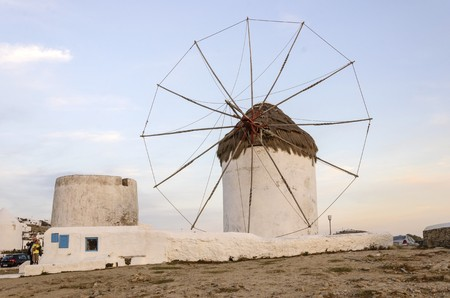 myconos: A windmill in Chora, Mykonos, Greece at sunset. Very traditional greek whitewashed architecture, a popular landmark and tourist destination on the island of winds against the deep blue sky and the Aegean sea. The wind mills are now decorative. Editorial