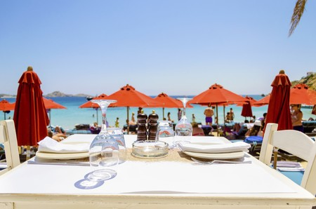 blue romance: A table set with plates, glasses and napkins on a beach bar restaurant and a view of the sun umbrellas and the blue sea in Mykonos, Greece. A greek island scene at the beach. Stock Photo