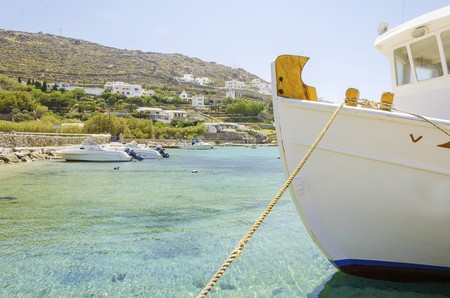 greek island: Fishing boats docked at Ornos beach in Greece. A view of the crystal clear blue sea at the greek island Mykonos, and whitewashed houses on the hill slope. A typical, idyllic summer holiday beach scene.