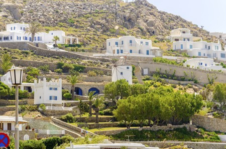 myconos: The cube whitewashed traditional houses and windmill in Ornos, Mykonos, Greece. Very typical greek island architecture on a rocky hill. Stock Photo