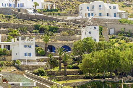 myconos: The cube whitewashed traditional houses and a windmill in Ornos, Mykonos, Greece. Very typical greek island architecture on a rocky hill. Editorial