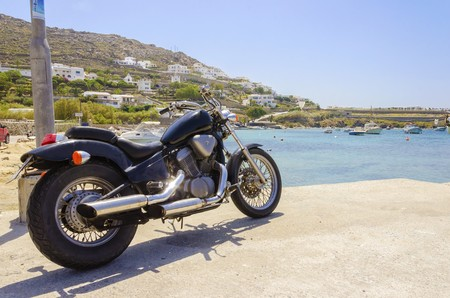 myconos: An old vintage motorbike parked at Ornos beach in Mykonos, Greece. A concept of freedom, summer and holiday vacations on the beautiful greek island and the crystal clear blue sea.