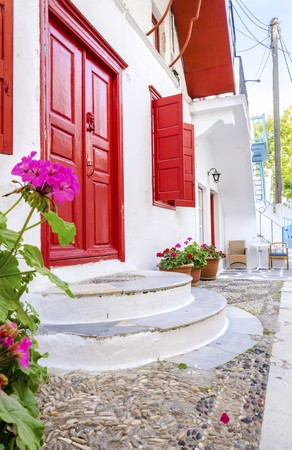 myconos: A very traditional alley view of the architecture in Chora, on the greek island Mykonos, Greece. A red door and windows, pink geranium flowers outside a whitewashed house and cobble paved street. Stock Photo