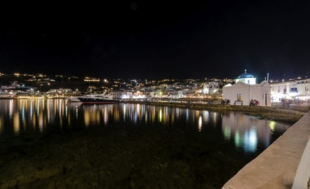 whitewashed: Night view of Chora port in Mykonos, Greece. Hora town cityscape lights reflected on the sea, whitewashed blue dome greek island church in the harbour and yachts anchored. A colourful and beautiful seascape.