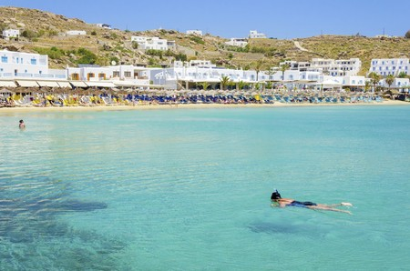 Platis Gialos beach on greek island Mykonos, Greece. A view of the crystal clear blue sea, sunbeds, sun umbrellas, golden sand, whitewashed houses and a woman snorkeling in the water on a summer day. Stock Photo