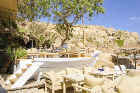snake bar: The famous Super paradise beach on the greek island Mykonos, Greece. A view of the golden sandy beach, ship bar, sofas, chairs and tables on a perfect summer holiday party place. Stock Photo