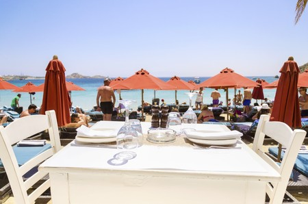 myconos: A table set with plates, glasses and napkins on a beach bar restaurant and a view of the sun umbrellas and the blue sea in Mykonos, Greece. A greek island scene at the beach. Stock Photo