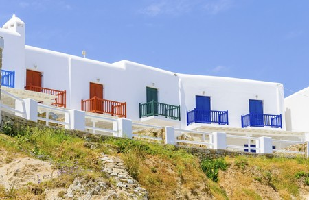 myconos: Trational whitewashed cubic beach greek island holiday apartments with blue, red and green wooden windows and blacony over a hill facing the sea in Mykonos, Greece on a summer day