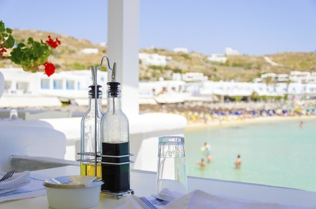 greek island: A table set with plates, glasses, olive oil and balsamic vinegar on a beach bar restaurant and a view of the blue sea in Mykonos, Greece. A greek island scene at the beach ready for lunch. Stock Photo