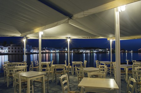 greek island: Night view of Chora and the port in Mykonos, Greece. Hora town cityscape lights reflected on the sea, through greek island restaurant with white wooden chairs and tables. A colourful and beautiful seascape.