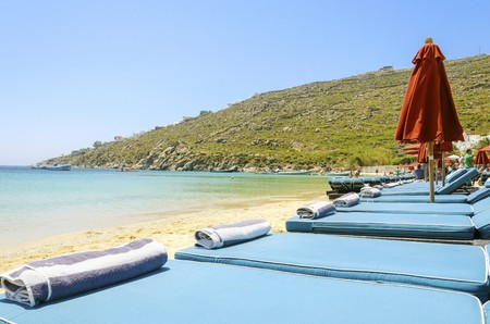 myconos: Sun beds with couchins, umbrellas, golden sand and the blue sea in Mykonos, Greece. A greek island summer holiday scene at the Psarou beach with a boat in the crystal clear water over a bushy hill.