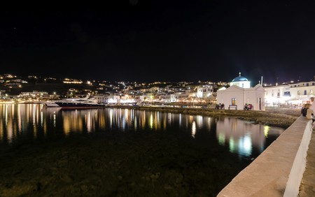 myconos: Night view of Chora port in Mykonos, Greece. Hora town cityscape lights reflected on the sea, whitewashed blue dome greek island church in the harbour and yachts anchored. A colourful and beautiful seascape.