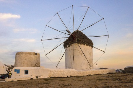 myconos: A windmill in Chora, Mykonos, Greece at sunset. Very traditional greek whitewashed architecture, a popular landmark and tourist destination on the island of winds against the deep blue sky and the Aegean sea. The wind mills are now decorative. Stock Photo