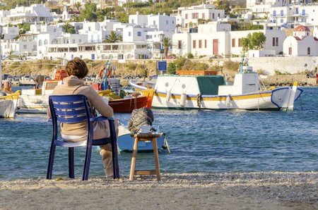 myconos: The coastline of Chora in Mykonos, Greece. A woman stting on the golden sand beach having coffee and gazing the view, typical greek island boats and whitewashed houses with colourful windows on the shore overlooking the Aegean sea and calm clean blue wate Stock Photo