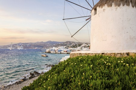 myconos: A windmill in Chora, Mykonos, Greece at sunset. Very traditional greek whitewashed architecture, a popular landmark and tourist destination on the island of winds against the colourful sky and the Aegean sea overlooking Little Venice. The wind mills are n Stock Photo