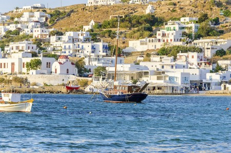 whitewashed: Colourful fishing and sail boats anchored on the Chora port in Mykonos, Greece. A view of a typical greek island harbour, whitewashed buildings on the hill and blue sea on a sunny day