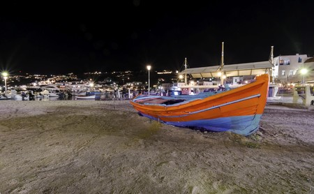 myconos: Night view of Chora port in Mykonos, Greece. Hora town cityscape lights reflected on the sea, a typical orange, blue greek island fishing boat in the harbour sandy shore and whitewashed buildings.