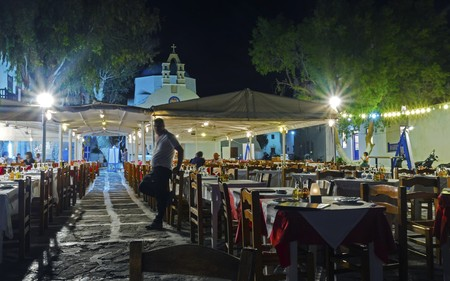 dinner cruise: Night view of a restaurant in Chora in Mykonos, Greece. A typical greek island restaurant with traditional wooden chairs and tables and whitewashed blue dome church in the background.