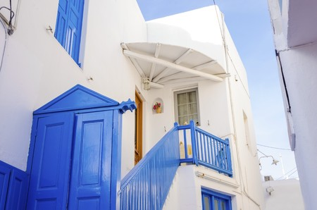myconos: A very traditional alley view of the architecture in Chora, on the greek island Mykonos, Greece. A blue door, fence and windows of a whitewashed house against the blue sky. Stock Photo