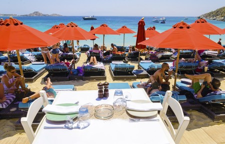 myconos: People on sun beds with couchins, umbrellas, golden sand, a table set and the blue sea in Mykonos, Greece. A greek island summer holiday scene at the Psarou beach with a boat in the crystal clear water over a bushy hill.