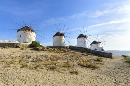 myconos: Four windmills in Chora, Mykonos, Greece. Very traditional greek whitewashed architecture, a popular landmark and tourist destination on the island of winds against the deep blue sky and the Aegean sea. The wind mills are now decorative.