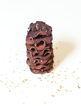 appetiser: A stack of thin round beetroot chips baked in the oven with oregano and salt piled on white background. A healthy, vegetarian, vegan, crispy snack appetiser for diet and clean eating.
