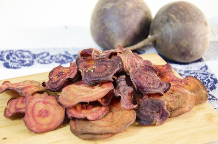 appetiser: Thin round beetroot chips baked in the oven with oregano, salt and raw beets on a chopping board and kitchen towel isolated in white background. A healthy, vegetarian, vegan, crispy snack appetiser for diet and clean eating.