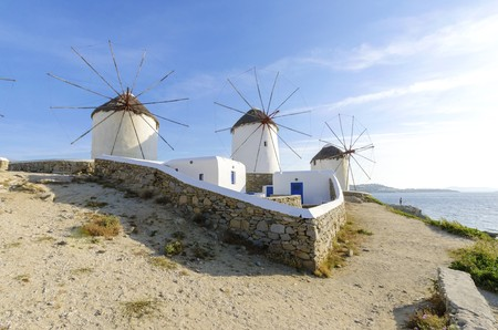 myconos: Three windmills in Chora, Mykonos, Greece. Very traditional greek whitewashed architecture, a popular landmark and tourist destination on the island of winds against the deep blue sky and the Aegean sea. The wind mills are now decorative. Stock Photo