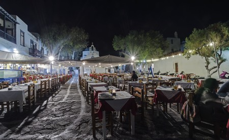 Night view of a restaurant in Chora in Mykonos, Greece. A typical greek island restaurant with traditional wooden chairs and tables and whitewashed blue dome church in the background.