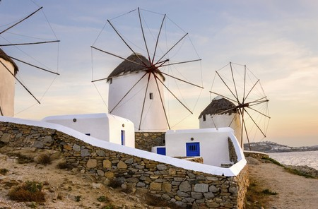 myconos: Three windmills in Chora, Mykonos, Greece at sunset. Very traditional greek whitewashed architecture, a popular landmark and tourist destination on the island of winds against the colourful sky and the Aegean sea. The wind mills are now decorative. Stock Photo