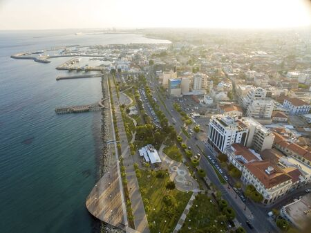 sea life centre: Aerial view of Molos Promenade on the coast of Limassol city in Cyprus. A view of the walk path surrounded by palm trees, pools of water, grass, the Mediterranean sea, piers, rocks urban skyline, old port and Marina.
