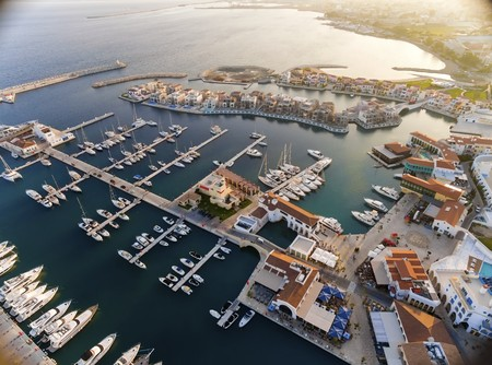 Aerial view of the beautiful Marina in Limassol city in Cyprus, the beach, boats, piers, villas and commercial area. A very modern, high end and newly developed space where yachts are moored and its perfect for a waterfront promenade.