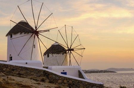 myconos: Two windmills in Chora, Mykonos, Greece at sunset. Very traditional greek whitewashed architecture, a popular landmark and tourist destination on the island of winds against the colourful sky and the Aegean sea. The wind mills are now decorative.
