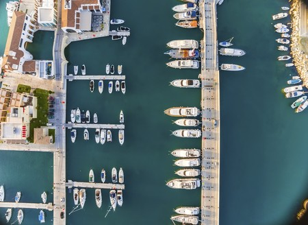 high end: Aerial view of the beautiful Marina in Limassol city in Cyprus, the boats lined up, piers, and commercial area from above. A very modern, high end and newly developed space where yachts are moored and its perfect for a waterfront promenade.