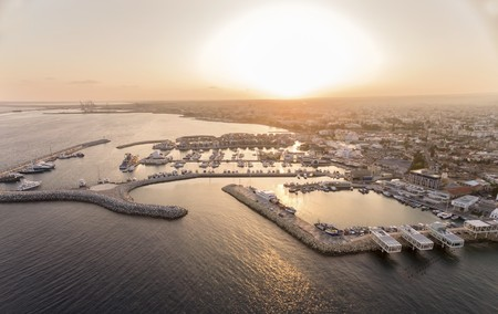 beach panorama: Aerial view of fishing boats docked at the Limassol old port (palio limani) in Cyprus at sunset, next to the Marina part of the ports authority. A view of the harbor, the mediterranean sea, the water, boat and fish nets and fishing equipment. Stock Photo