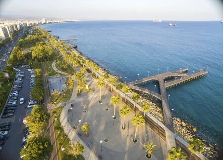 Aerial view of Molos Promenade on the coast of Limassol city in Cyprus. A view of the walk path surrounded by palm trees, pools of water, grass, the Mediterranean sea, piers, rocks and urban skyline.