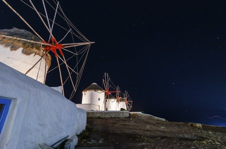 myconos: Night view of five windmills in Chora, Mykonos, Greece. Very traditional greek whitewashed architecture, a popular landmark and tourist destination on the island of winds on a clear night with stars. The wind mills are now decorative. Stock Photo