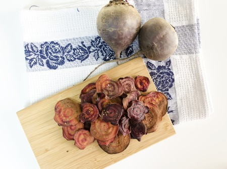 appetiser: Top view of thin round beetroot chips baked in the oven with oregano, salt and raw beets on a chopping board and kitchen towel isolated in white background. A healthy, vegetarian, vegan, crispy snack appetiser for diet and clean eating.