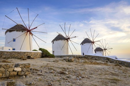 myconos: Four windmills in Chora, Mykonos, Greece at sunset. Very traditional greek whitewashed architecture, a popular landmark and tourist destination on the island of winds against the deep blue sky and the Aegean sea. The wind mills are now decorative.