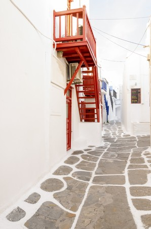 myconos: A very traditional alley view of the architecture in Chora, on the greek island Mykonos, Greece. A red door, fence and windows and straicase outside a whitewashed house and cobble paved street.