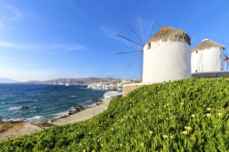 myconos: Wiindmills in Chora, Mykonos, Greece. Very traditional greek whitewashed architecture, a popular landmark and tourist destination on the island of winds against the deep blue sky and the Aegean sea overlooking Little Venice. The wind mills are now decorat Stock Photo