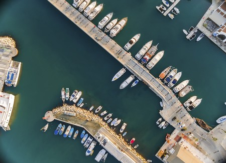 lined up: Aerial view of the beautiful Marina in Limassol city in Cyprus, the boats lined up, piers, and commercial area from above. A very modern, high end and newly developed space where yachts are moored and its perfect for a waterfront promenade.