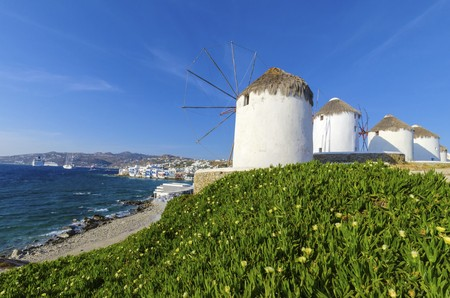 myconos: Four windmills in Chora, Mykonos, Greece. Very traditional greek whitewashed architecture, a popular landmark and tourist destination on the island of winds against the deep blue sky and the Aegean sea overlooking Little Venice. The wind mills are now dec