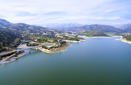 Aerial view of the earthfill dam (aka Embankment Dam) in Yermasoyia, Limassol, Cyprus. A view of the bridge leading to the mountains, the water reservoir, artificial lake and the nature trails in Germasogia area.