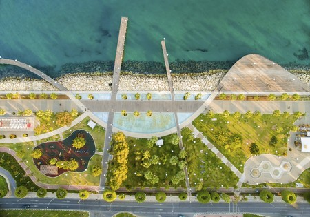 Aerial view of Molos Promenade on the coast of Limassol city in Cyprus. A view of the walk path surrounded by palm trees, pools of water, grass, boardwalk, the Mediterranean sea, piers, rocks and urban skyline.