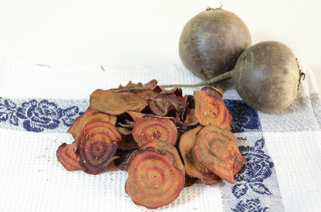 Thin round beetroot chips baked in the oven with oregano,salt and ripe beet roots on a kitchen towel isolated in white background. A healthy, vegetarian, vegan, crispy snack appetiser for diet and clean eating.