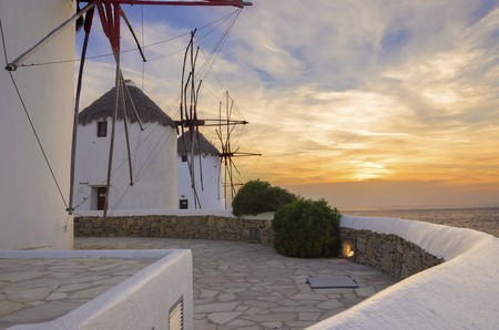 myconos: Three windmills in Chora, Mykonos, Greece at sunset. Very traditional greek whitewashed architecture, a popular landmark and tourist destination on the island of winds against the deep blue sky and the Aegean sea. The wind mills are now decorative. Stock Photo