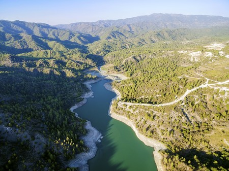 Aerial view of Diarizos river in Paphos, Cyprus. The river cutting through the green valley and lush forest of laona mountain leading to the Venetian bridge from the Arminou reservoir.