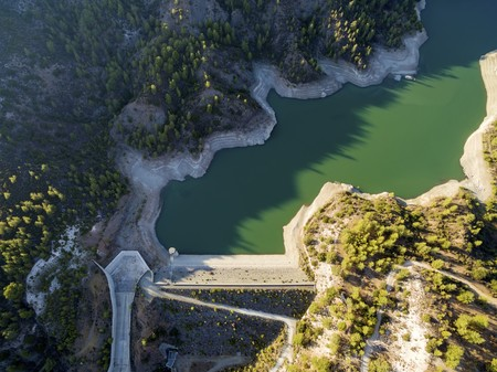 Aerial view of the embankment (earthfill  rockfill) dam in Arminou, Paphos, Cyprus. A terrain reservoir of the river Diarizos in Pafos cutting through the green valley and lush forest of laona mountain leading to the Venetian bridge.