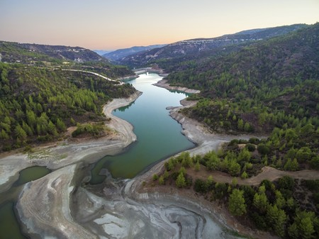 Aerial view of Diarizos river at sunset in Paphos, Cyprus. The river cutting through the green valley and lush forest of laona mountain leading to the Venetian bridge from the Arminou reservoir.